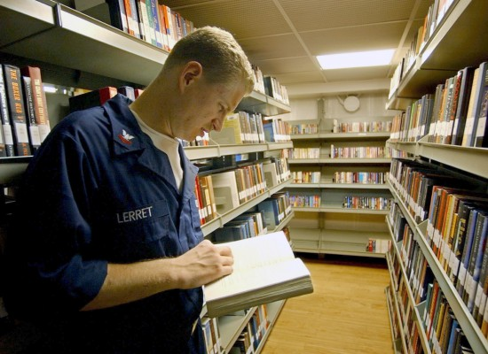 Photo: Reading in the library of the USS Harry Truman via Wikipedia and US Navy